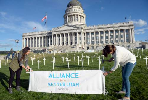 Al Hartmann  |  The Salt Lake Tribune Lauren Howells, left, and Tillie McInnis place 361 crosses on the front lawn of the Utah State Capitol Thursday Oct. 21 for Alliance for a Better Utah to make a visual point for their press conference.  Today marks 657 days since the Utah Legislature had the first opportunity to grant access to affordable healthcare for thousands of Utahns most in need. Better Utah estimates that as many as 361 Utahns (represented by the rows of crosses) have died because they don't have access to affordable healthcare.