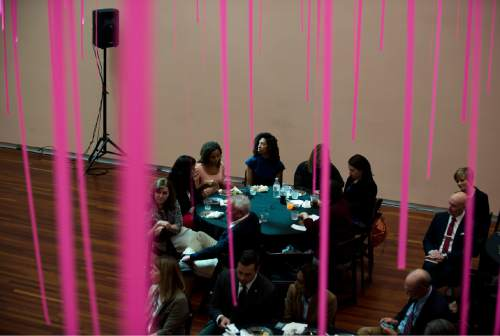 "Lennie Mahler  |  The Salt Lake Tribune  People eat lunch preceding an address from LDS Elder Joseph W. Sitati at the ""Black, White, and Mormon"" conference at the Utah Museum of Fine Arts, Friday, Oct. 9, 2015. The pink ribbons are part of an exhibit by artist Tony Feher."