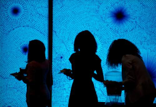 "Lennie Mahler  |  The Salt Lake Tribune  Women move get refreshments during a luncheon preceding an address from LDS Elder Joseph W. Sitati at the ""Black, White, and Mormon"" conference at the Utah Museum of Fine Arts, Friday, Oct. 9, 2015. The window is part of an exhibit by artist Tony Feher."