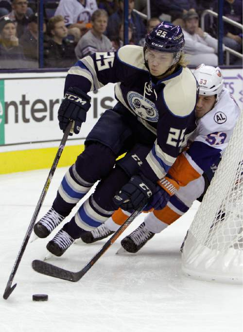 Columbus Blue Jackets' William Karlsson, of Sweden, left, carries the puck behind the net as New York Islanders' Casey Cizikas defends during the first period of an NHL hockey game Tuesday, Oct. 20, 2015, in Columbus, Ohio. (AP Photo/Jay LaPrete)