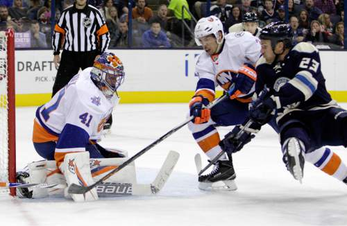 New York Islanders' Jaroslav Halak, left, of Slovakia, makes a save as teammate Travis Hamonic, center, and Columbus Blue Jackets' David Clarkson fight for position during the second period of an NHL hockey game Tuesday, Oct. 20, 2015, in Columbus, Ohio. (AP Photo/Jay LaPrete)