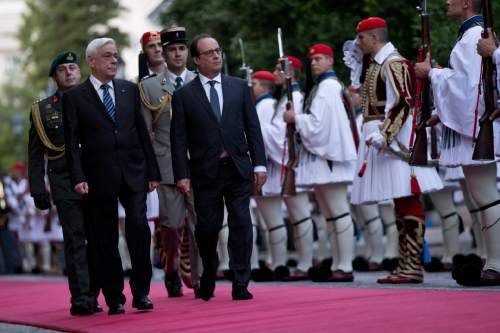 Greek President Prokopis Pavlopoulos, left, and his French counterpart Francois Hollande review the Presidential guard during a welcome ceremony in Athens, Thursday, Oct. 22, 2015. Hollande is in Greece for a two-day visit, as Greece seeks help from European rescue lenders for relief on its massive bailout debts. (AP Photo/Petros Giannakouris)