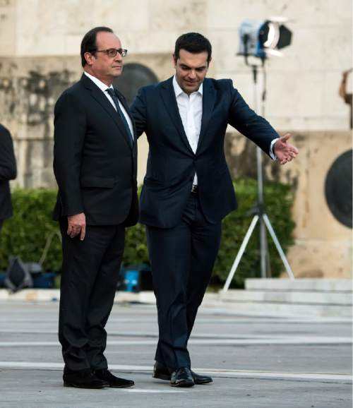 Greece's Prime Minister Alexis Tsipras, right, gestures as French President Francois Hollande prepares to lay a wreath at the tomb of the unknown solider in Athens on Thursday, Oct. 22, 2015. Hollande arrived in Athens for a two-day visit Thursday, as Greece seeks help from European rescue lenders for relief on its massive bailout debts.(Nikos Chalkiopoulos/InTime News via AP)  GREECE OUT