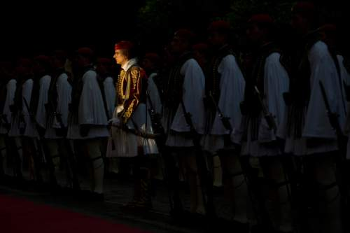 Greek presidential guards stand on duty prior a welcome ceremony of the French President  Francois Hollande in Athens, Thursday, Oct. 22, 2015. Hollande is in Greece for a two-day visit, as Greece seeks help from European rescue lenders for relief on its massive bailout debts. (AP Photo/Petros Giannakouris)