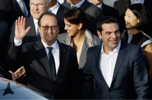 French President Francois Hollande, left, waves to the photographers as he escorted by Greece's Prime minister Alexis Tsipras, right, after his arrival at Athens airport on Thursday, Oct. 22, 2015. Hollande is heading to Athens for a two-day visit, as Greece seeks help from European rescue lenders for relief on its massive bailout debts. (AP Photo/Thanassis Stavrakis)