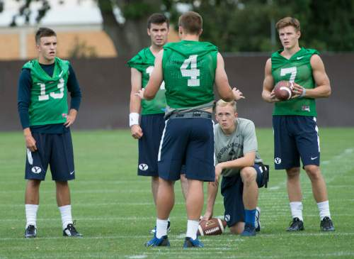 Leah Hogsten  |  The Salt Lake Tribune Quarterback Taysom Hill talks with fellow backup quarterbacks l-r Koy Detmer, Jr., Tanner Mangum and Beau Hoge during Brigham Young University's first practice of fall football camp, August 8, 2015.