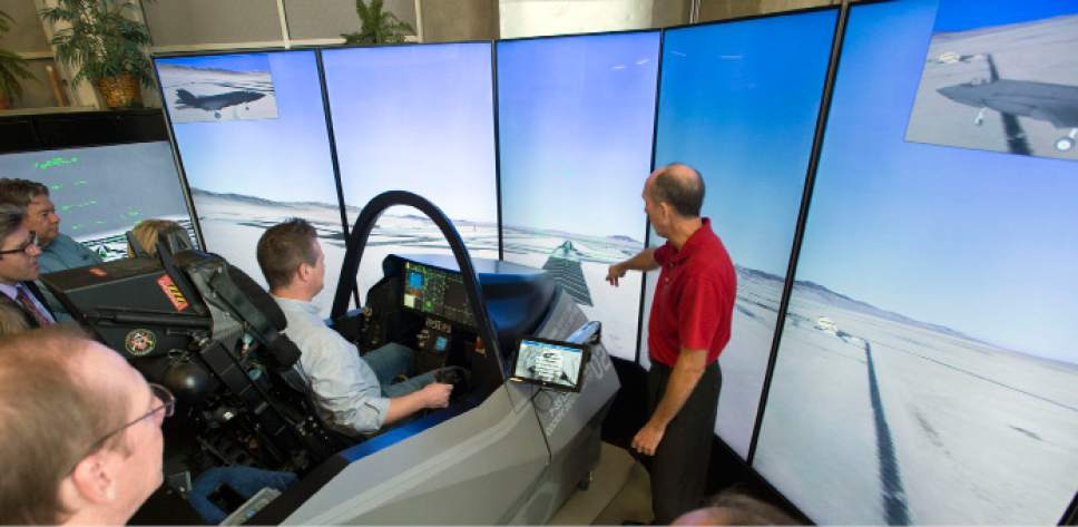 "Steve Griffin  |  The Salt Lake Tribune  Former F-16 pilot Eric Best, call sign ""PJ,"" left, instructs Salt Lake Tribune reporter Nate Carlisle as he tries t the F-35 flight simulator at the  Kennecott Building on the University of Utah campus in Salt Lake City on Oct. 9, 2015."