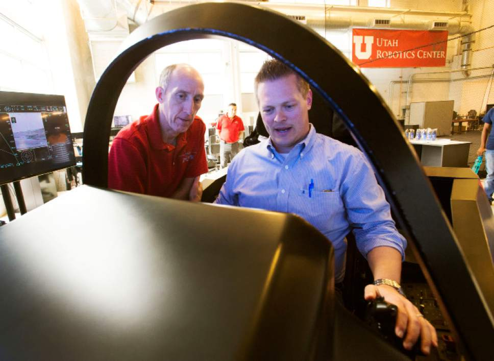 "Steve Griffin  |  The Salt Lake Tribune Former F-16 pilot Eric Best, call sign ""PJ,"" left, instructs Salt Lake Tribune reporter Nate Carlisle as he tries out the F-35 flight simulator at the  Kennecott Building on the University of Utah campus in Salt Lake City earlier this month."