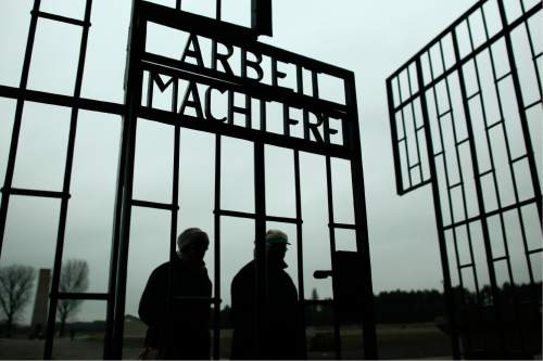 People walk through the gate of the Sachsenhausen Nazi death camp with the phrase 'Arbeit macht frei' (work sets you free) at the eve of the International Holocaust Remembrance Day, in Oranienburg, about 30 kilometers,  (18 miles) north of Berlin, Monday, Jan. 26, 2015. The International Holocaust Remembrance Day marks the liberation of the Auschwitz Nazi death camp on Jan. 27, 1945.  (AP Photo/Markus Schreiber)