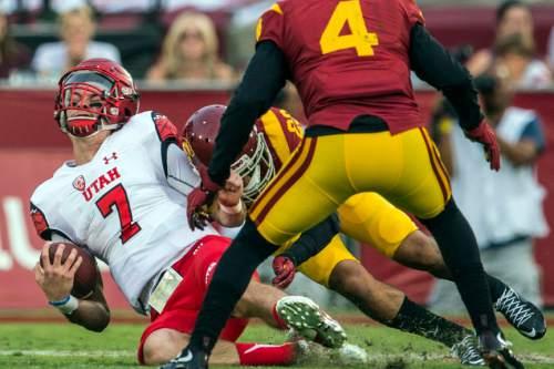 Chris Detrick     The Salt Lake Tribune Utah Utes quarterback Travis Wilson (7) is tackled by USC Trojans cornerback Jonathan Lockett (23) during the game at the Los Angeles Memorial Coliseum Saturday October 24, 2015.