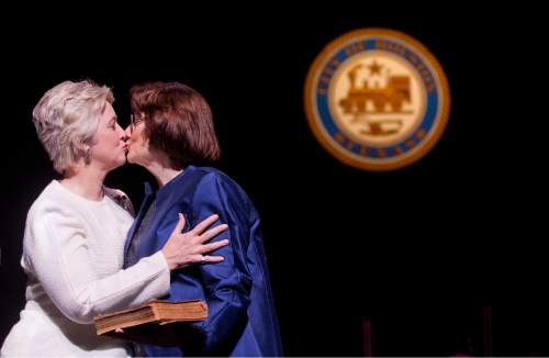 FILE - In this Thursday, Jan. 2, 2014 file photo, Houston Mayor Annise Parker, left, kisses her partner, Kathy Hubbard, after Parker was sworn in for her third term as mayor during the inauguration ceremony for Parker, City Controller Ronald Green and the 16-member Houston City Council at Wortham Theater Center in Houston. After a drawn-out showdown between Houston's popular lesbian mayor and a coalition of conservative pastors, on Nov. 3, 2015, voters in the nation's fourth-largest city will decide whether to establish nondiscrimination protections for gay and transgender people. (Johnny Hanson/Houston Chronicle via AP)  MANDATORY CREDIT