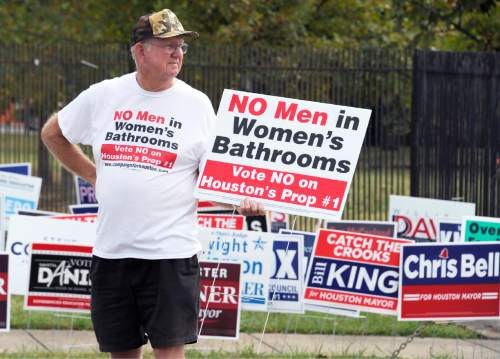 A man urges people to vote against the Houston Equal Rights Ordinance outside an early voting center in Houston on Wednesday, Oct. 21, 2015. The contested ordinance is a broad measure that would consolidate existing bans on discrimination tied to race, sex, religion and other categories in employment, housing and public accommodations, and extend such protections to gays, lesbians, bisexuals and transgender people. (AP Photo/Pat Sullivan)
