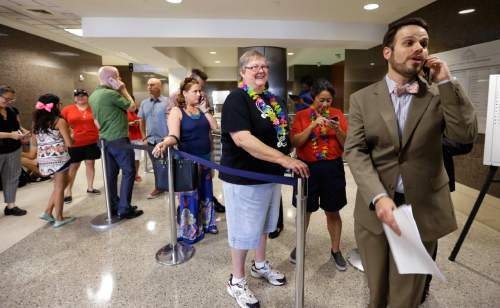 FILE - In this Friday, June 26, 2015 file photo, couples wait outside the Harris County Personal Records Office to get marriage licenses in Houston just hours after the U.S. Supreme Court announced their decision that same-sex couples have a right to marry in all 50 states. After a drawn-out showdown between Houston's popular lesbian mayor and a coalition of conservative pastors, on Nov. 3, 2015, voters in the nation's fourth-largest city will decide whether to establish nondiscrimination protections for gay and transgender people. (AP Photo/Pat Sullivan, File)