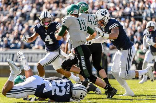 Trent Nelson     The Salt Lake Tribune Brigham Young Cougars defensive lineman Bronson Kaufusi (90) sacks Wagner Seahawks quarterback Alex Thomson (19) as BYU hosts Wagner, NCAA football at LaVell Edwards Stadium in Provo, Saturday October 24, 2015.