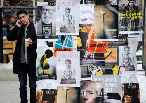 Sundance festivalgoer Zane Miyamoto, of Los Angeles, talks on his cell phone next to posters advertising festival films during day two of the 2015 Sundance Film Festival on Friday, Jan. 22, 2015, in Park City, Utah. (Photo by Chris Pizzello/Invision/AP)