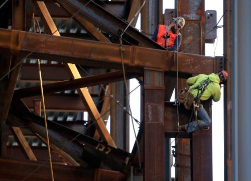 In this Oct. 23, 2015 file photo, iron workers help to build the new Comcast Innovation and Technology Center in Philadelphia. The Commerce Department issues the first of three estimates of how the U.S. economy performed in the July-September quarter on Thursday, Oct. 29, 2015. (AP Photo/Matt Rourke, File)