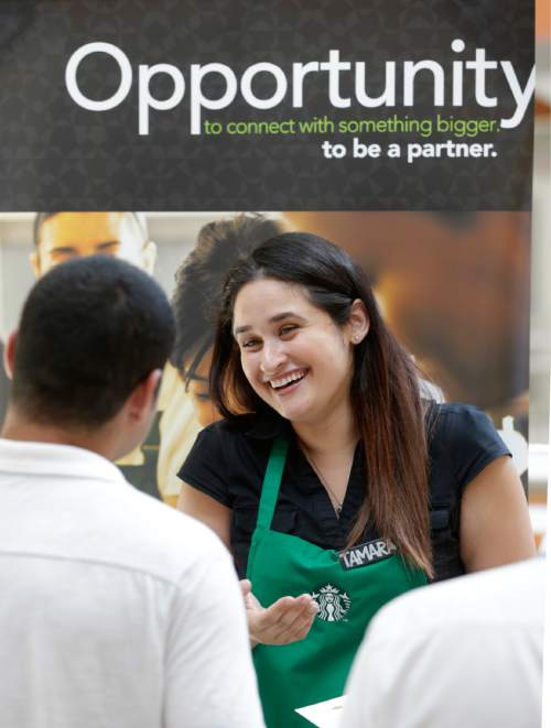 In this Tuesday, Oct. 6, 2015 photo, Starbucks assistant store manager Tammy Munoz talks with a job applicant during a job fair at Dolphin Mall in Miami. The Commerce Department issues the first of three estimates of how the U.S. economy performed in the July-September quarter on Thursday, Oct. 29, 2015. (AP Photo/Wilfredo Lee)