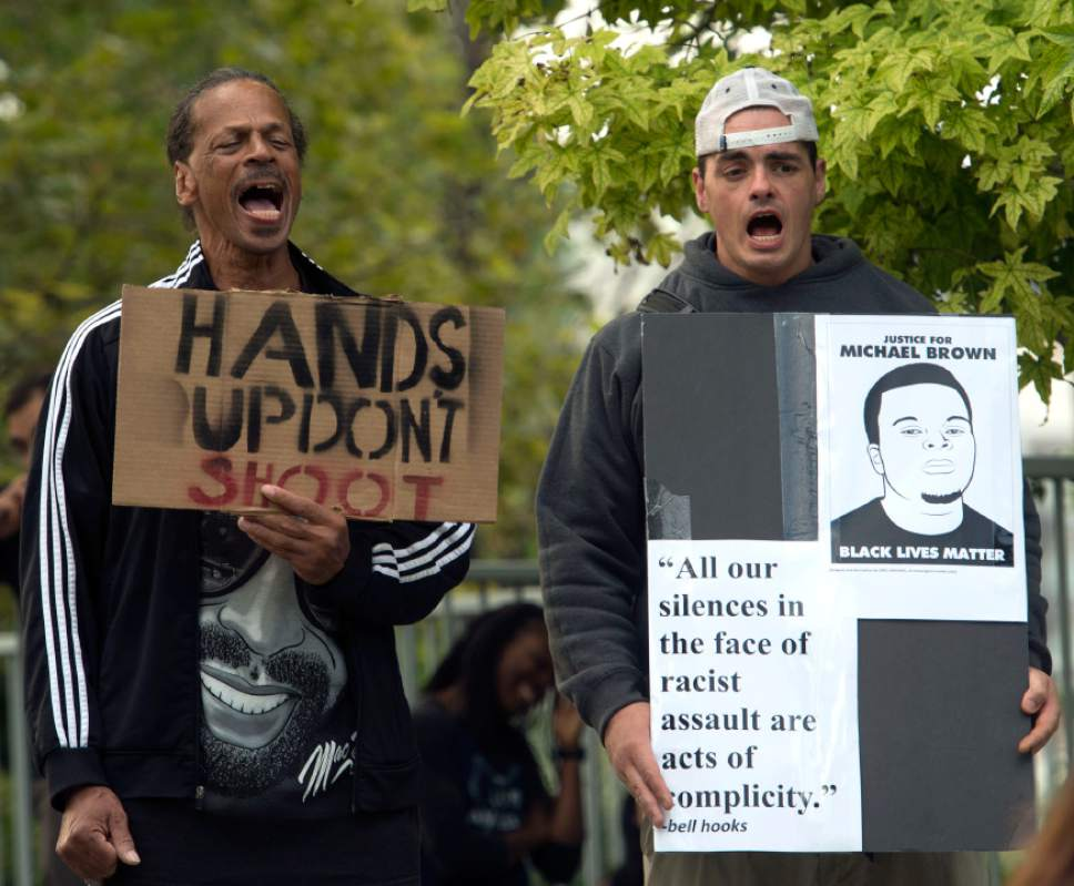 Rick Egan  |  The Salt Lake Tribune  Oscar Ross, and Damon Harris shout along with other protestors, in solidarity with Mike Brown, Dillon Taylor, Danielle Willard and others who they feel were murdered unjustly. Monday, August 25, 2014.