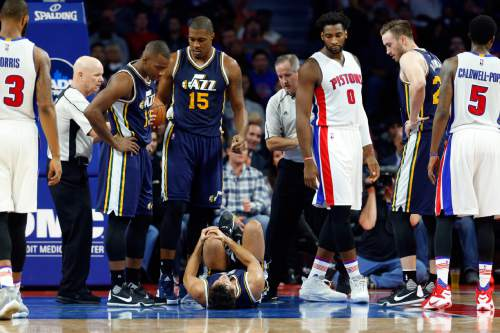 Utah Jazz guard Raul Neto (25) holds his knee on the floor in the first half of an NBA basketball game against the Detroit Pistons, Wednesday, Oct. 28, 2015 in Auburn Hills, Mich. (AP Photo/Paul Sancya)