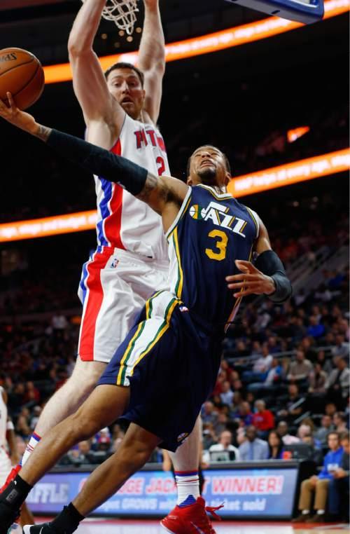 Utah Jazz guard Trey Burke (3) drives against Detroit Pistons forward Aron Baynes (12) in the first half of an NBA basketball game Wednesday, Oct. 28, 2015, in Auburn Hills, Mich. (AP Photo/Paul Sancya)