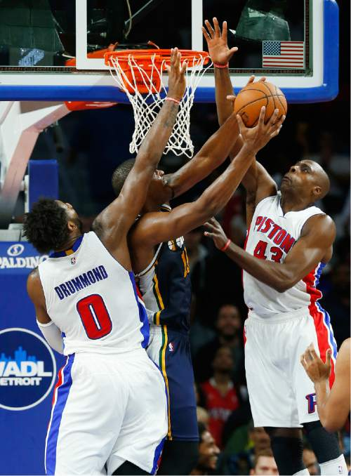 Utah Jazz forward Derrick Favors (15) drives against Detroit Pistons center Andre Drummond (0) and Anthony Tolliver (43) in the second half of an NBA basketball game Wednesday, Oct. 28, 2015, in Auburn Hills, Mich. (AP Photo/Paul Sancya)