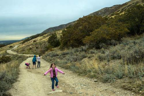 Chris Detrick  |  The Salt Lake Tribune Sophie Mason, 5, plays along along Firebreak Road on Twin Hollow Mountain Wednesday October 28, 2015. In the background is Brandon Mason, 14, Lexie Mason, 8 and Kate Mason, 12. A pair of Utah developers are seeking a public land swap in the Bountiful foothills that they say will accommodate public access and conservation in two key spots.  Some nearby residents, however, fear the plan would invite high-density residential growth in the wrong place.