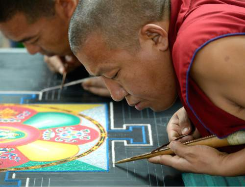 Al Hartmann  |  The Salt Lake Tribune Buddhist monks from the Drepung Loseling Monastery create an intricate Mandala sand painting one grain of sand at a time at the Parliament of the World's Religions inside the Salt Palace Convention Center on Friday. It takes monks 3-5 days to complete a Mandala. An estimated 9,500 people from 50 religions will attend the event which runs through Monday.