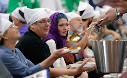 Al Hartmann  |  The Salt Lake Tribune Several thousand attending the Parliament of the World's Religions wearing head covering sit together as equals on the floor of the Salt Palace Convention Center Friday, Oct. 16 and served food by members of the Sikh religious community at a traditional Langar.  Langar is a 500-year-old Sikh religion tradition where vegetarian food is served to all for free, regardless of religion or class.  Langar expresses the ideals of community, sharing and oneness of mankind.