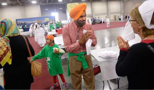 "Al Hartmann  |  The Salt Lake Tribune Tarlochan Gill of Salt Lake City greets the several thousand attending the Parliament of the World's Religions ""Langar"" at the Salt Palace Convention Center Friday, Oct. 16.  Dozens of members of the Sikh religion served the conference attendees sitting together on the floor in the 500-year-old Sikh religion tradition where vegetarian food is served to all for free, regardless of religion or class.  Langar expresses the ideals of community, sharing and oneness of mankind."