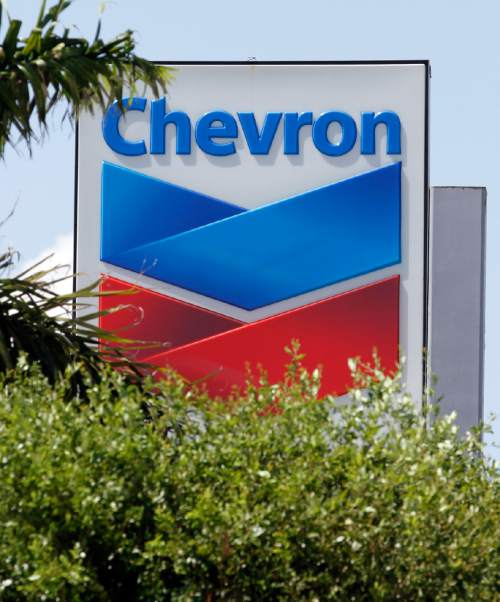 FILE - This Aug. 20, 2012 photo shows a Chevron sign in Miami. Chevron Corp. is cutting up to 7,000 jobs as it deals with lower oil prices that are cutting deeply into profit. The company said Friday, Oct. 30, 2015  that it would cut capital and exploratory spending next year by one-fourth, with further cuts in 2017 and 2018 depending on the oil industry's condition then.  (AP Photo/Alan Diaz)