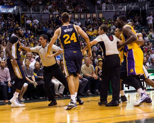 A referee separates Utah Jazz forward Trevor Booker (33), left, and Los Angeles Lakers center Roy Hibbert (17), far right, after an altercation between the players during the second half of an NBA preseason basketball game, Tuesday, Oct. 6, 2015, in Honolulu.  Booker was ejected from the game and a technical foul was called on Hibbert.  (AP Photo/Marco Garcia)