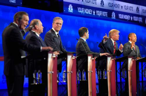 John Kasich, left, and Donald Trump, second from right, argue across fellow candidates during the CNBC Republican presidential debate at the University of Colorado, Wednesday, Oct. 28, 2015, in Boulder, Colo. (AP Photo/Mark J. Terrill)