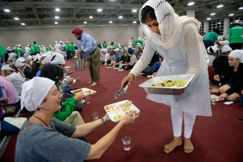 Al Hartmann  |  The Salt Lake Tribune Several thousand attending the Parliment of the World's Religions wear head covering and sit together as equals on the floor of the Salt Palace Convention Center on Friday while members of the Sikh religious community serve food at a traditional Langar. Langar is a 500-year-old Sikh religion tradition where vegetarian food is served to all for free, regardless of religion or class. Langar expresses the ideals of community, sharing and oneness of mankind.