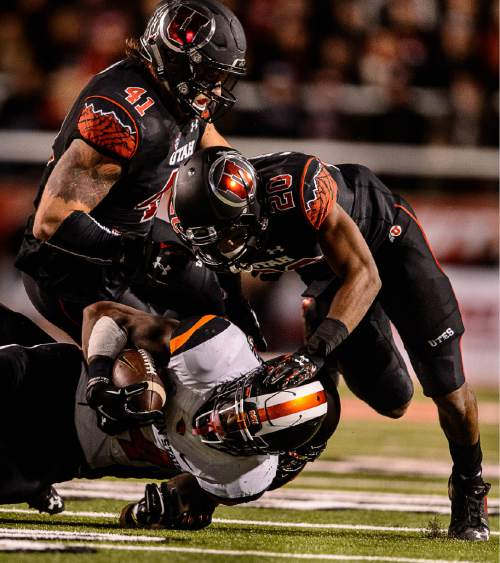 Trent Nelson  |  The Salt Lake Tribune Utah Utes linebacker Jared Norris (41) and Utah Utes defensive back Marcus Williams (20) bring down Oregon State Beavers running back Storm Woods (24) as the University of Utah hosts Oregon State, NCAA football at Rice-Eccles Stadium in Salt Lake City, Saturday October 31, 2015.