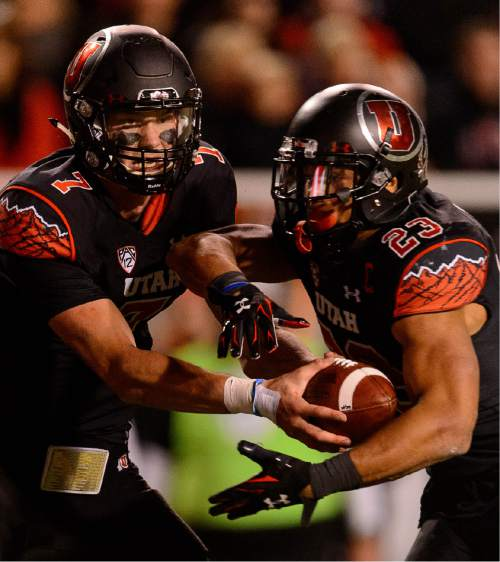 Trent Nelson  |  The Salt Lake Tribune Utah Utes quarterback Travis Wilson (7) hands off to Utah Utes running back Devontae Booker (23) as the University of Utah hosts Oregon State, NCAA football at Rice-Eccles Stadium in Salt Lake City, Saturday October 31, 2015.