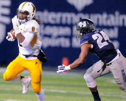 Wyoming running back Brian Hill, left, carries the ball as Utah State safety Marwin Evans, right, defends, Friday, Oct. 30, 2015, in Logan, Utah. (Eli Lucero/Herald Journal via AP)