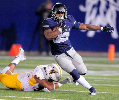 Utah State running back Devante Mays, right, runs past Wyoming defensive end Eddie Yarbrough, left, Friday, Oct. 30, 2015, in Logan, Utah. (Eli Lucero/Herald Journal via AP)