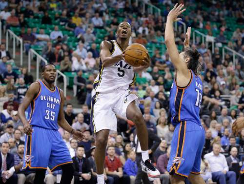 Utah Jazz guard Rodney Hood (5) goes to the basket between Oklahoma City Thunder's Steven Adams (12) and  Kevin Durant (35) during the second quarter of an NBA preseason basketball game Tuesday, Oct. 20, 2015, in Salt Lake City. The Thunder won 113-102. (AP Photo/Rick Bowmer)