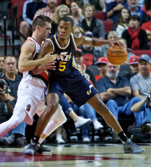 Utah Jazz guard Rodney Hood, right, posts up against Portland Trail Blazers guard Pat Connaughton during the first half of an NBA preseason basketball game in Portland, Ore., Sunday, Oct. 18, 2015. (AP Photo/Craig Mitchelldyer)