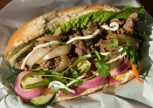Rick Egan  |  The Salt Lake Tribune  Garlic-butter steak banh mi sandwich: steak with garlic-butter, mayo, lettuce, cucumber, pickled daikon and carrots, cilantro, black pepper, tomatoes, onion vinaigrette, at Little Saigon, a new Vietnamese restaurant in Sugar House.