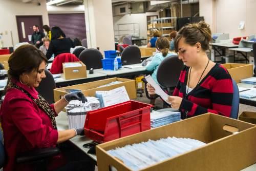 Chris Detrick  |  The Salt Lake Tribune Gissell Jimenez, left, and Natasha Lining open and prepare ballots for tabulation at the Salt Lake County Government Center Wednesday November 4, 2015.