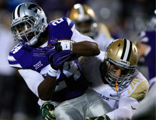 Kansas State running back Charles Jones (24) is tackled by Baylor linebacker Grant Campbell, right, during the first half of an NCAA college football game in Manhattan, Kan., Thursday, Nov. 5, 2015. (AP Photo/Orlin Wagner)