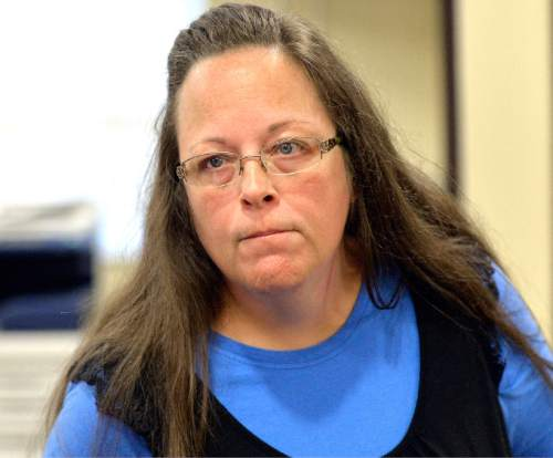 FILE - In this Tuesday, Sept. 1, 2015, file photo, Rowan County Clerk Kim Davis listens to a customer following her office's refusal to issue marriage licenses at the Rowan County Courthouse in Morehead, Ky. Davis, who spent five days in jail for defying a series of federal court orders, filed a lawsuit against Gov. Steve Beshear, alleging he violated her religious freedom by asking clerks to comply with the U.S. Supreme Court's decision, which effectively legalized gay marriage across the nation. Beshear reiterated a request Tuesday, Sept. 29, that a judge toss the suit. (AP Photo/Timothy D. Easley, File)