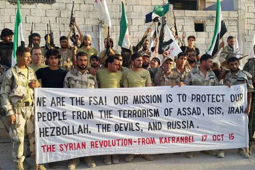 In this photo released on October 17, 2015, and provided by the Fursan al-Haq Syrian rebel brigade, which has been authenticated based on its contents and other AP reporting, Free Syrian Army fighters of Fursan al-Haq Brigade hold a banner, in Kafranbel , Idlib province, northern Syria. TDespite a month of heavy battering by Russian airstrikes, Syria's rebels have so far been able to fend off offensives by government forces trying to retake territory from the rebel's heartland. The fierce fighting shows how even greater backing from Syrian President Bashar Assad's international allies is not swiftly tipping the conflict in his favor.(Fursan al-haq Rebel Brigade via AP)