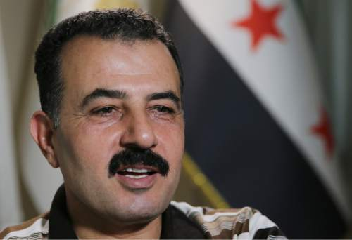In this picture taken on Friday Oct. 23, 2015, Free Syrian Army Col. Ahmad Hamada, spokesman of the supreme command of the Syrian revolution, speaks during an interview with The Associated Press, at the Turkish-Syrian border of Reyhanli town, southern Turkey.  Despite a month of heavy battering by Russian airstrikes, Syria's rebels have so far been able to fend off offensives by government forces trying to retake territory from the rebel's heartland. The fierce fighting shows how even greater backing from Syrian President Bashar Assad's international allies is not swiftly tipping the conflict in his favor. (AP Photo/Hussein Malla)