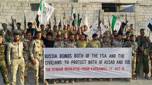 In this photo released on October 17, 2015, and provided by the Fursan al-Haq Syrian rebel brigade, which has been authenticated based on its contents and other AP reporting, Free Syrian Army fighters of Fursan al-Haq Brigade hold a banner, in Kafranbel, Idlib province, northern Syria. Despite a month of heavy battering by Russian airstrikes, Syria's rebels have so far been able to fend off offensives by government forces trying to retake territory from the rebel's heartland. The fierce fighting shows how even greater backing from Syrian President Bashar Assad's international allies is not swiftly tipping the conflict in his favor. (Fursan al-haq Rebel Brigade via AP)