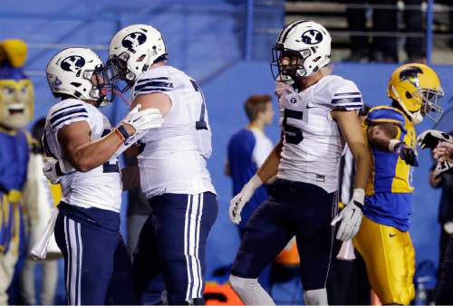 BYU running back Algernon Brown, left, is hugged by a teammate after his rushing touchdown against San Jose State during the first half of an NCAA college football game Friday, Nov. 6, 2015, in San Jose, Calif. (AP Photo/Marcio Jose Sanchez)