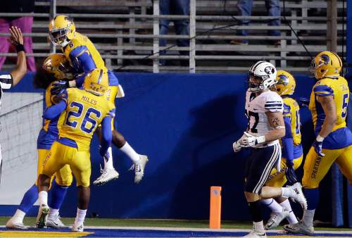 San Jose State cornerback Cleveland Wallace III, top left, is lifted by teammates after scoring on a 61-yard interception return during the first half of an NCAA college football game against BYU on Friday, Nov. 6, 2015, in San Jose, Calif. (AP Photo/Marcio Jose Sanchez)
