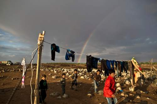 A rainbow stretches across the sky behind Syrian refugee children playing in an informal tented settlement near the Syrian border on the outskirts of Mafraq, Jordan, Thursday, Oct. 29, 2015. (AP Photo/Muhammed Muheisen)
