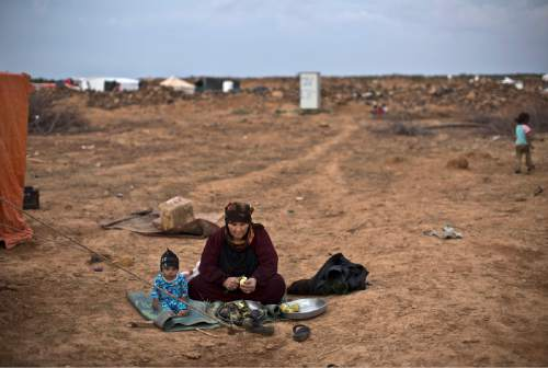 A Syrian refugee child sits next to his grandmother while peeling aubergine for dinner, outside their tent at an informal tented settlement near the Syrian border on the outskirts of Mafraq, Jordan, Wednesday, Oct. 28, 2015. (AP Photo/Muhammed Muheisen)